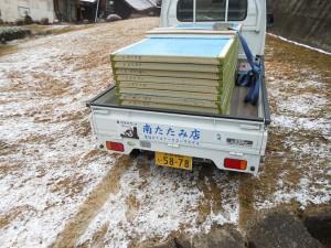 畳を積んだ軽トラと雪